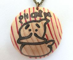 """Necklace with wooden pendant with the words """"oh crêpe"""" and a rubber duck."""
