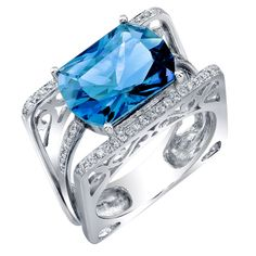 1stdibs | Swiss Blue Topaz Diamond Gold Ring. Stunning Swiss-Blue Topaz ring accented by fifty-four brilliant-cut round Diamonds, extending to angular shank, weighing approx. 0.27 ct., D-ended rectangular facet-cut Topaz measures approx. 14mmx10mm, approx. weight 7.33 ct..; mounted in 14k white gold with open pierced gallery. Ring size: 7. Beautiful and fun to wear!