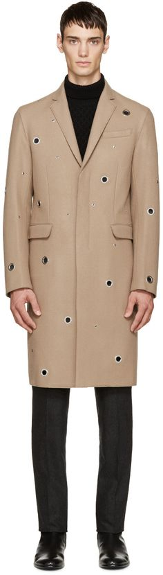 Long sleeve felted wool coat in beige. Silver-tone eyelet features in various sizes throughout. Notched lapel collar. Button closure at front. Welt pocket at breast. Flap pockets at front. Unlined. Tonal stitching.