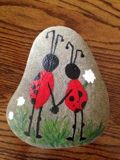 pintar con acrilico, piedra natural, dibujo de mariquitas con dos piernas agarrados de la mano, flores blancos, idea para niños