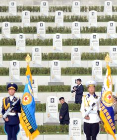 North Korean leader Kim Jong Un, center, walks through a cemetery for Korean War veterans on Thursday, July 25, 2013 in Pyongyang, North Korea marking the 60th anniversary of the signing of the armistice that ended hostilities on the Korean peninsula. (AP Photo/Kyodo News)