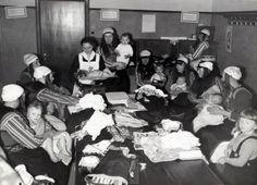 Zuigelingenzorg in overvolle ruimte. Moeders in klederdracht krijgen les in babyverzorging. Marken, 20 december 1941.
