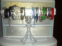 DIY bracelet display. I would take a glass candle stick and a paper towel roll n make this ~Ash