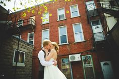 bride and groom brick wall