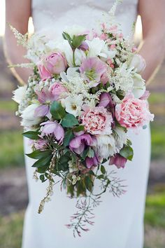Gorgeous Wedding Bouquet Showcasing: Pink Roses, Pink Fringed Tulips, Pink Hellebores, Pink Hypericum Berries, White Astilbe, White Protea, White Freesia, Several Varieties Of Greenery & Foliage