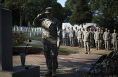 Pvt. John Schena, with the 2nd Battalion 1st Brigade of the Georgia State Defense Force, salutes after placing a rose at a Pearl Harbor Memorial at Marietta National Cemetery on Memorial Day, Monday, May 26, 2014, in Marietta, Ga.