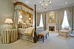 Beautiful bedroom, nice dressed bedside table, chandelier, fireplace, curtains, chairs.