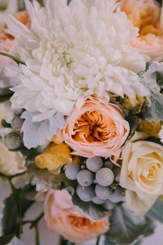 White, peach & lemon flowers with berries - Image by Chris Barber - Justin Alexander Wedding Dress For A Winter Wedding At Compton Verney Art Gallery With Groom In Reiss And Bridesmaids In Embellished Dresses From Miss Selfridge With Images By Chris Barber And Videography By Simon Clarke Films
