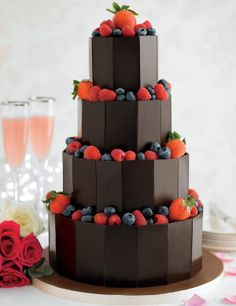 A beautiful 4 tier dark chocolate wedding cake with chocolate ganache and sprinkles, finished with dark chocolate plaques.