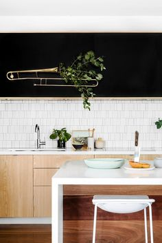 Trombone Planter : Repurposed Wall Art. This kitchen is made whimsical with its unique repurposing of a popular band instrument – the sliding trombone. Doubling as 3D wall art and a planter, this trombone breaths new life into an otherwise minimalist kitchen. #cleverlife
