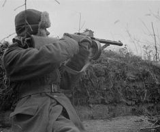 Soldier firing his weapon during battle. Svir river, 12 Nov 1942.