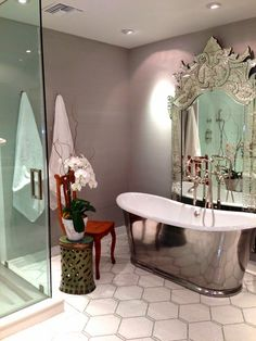 I love the gray walls and the pop of fancy with the intricate mirror behind the freestanding tub