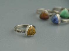 This silver Ocean Jasper ring looks great alone, or stacked up with several!  I have hand fabricated the ring from sterling silver, giving it a texture of hammered lines. It features a 10x10mm triangle (or trillion) shaped mustard yellow Ocean Jasper cabochon, bezel set in fine and sterling silver. The ring has a brushed patina finish to highlight the texture.  US Size 8.25  Fourth photo is an example of size and style but shows a different stone. Last photo shows examples of other colored…