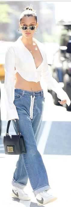 Who made  Bella Hadid's blue jeans, white sneakers, tie backless top, and black handbag?