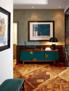 """In a young couple's home in Paris's 16th arrondissement, interior designer Laura Gonzalez found what she calls """"the perfect blend between the classical architecture of the apartment and modern details."""" In the entry, a vintage bench upholstered in a velvet fabric by Dedar matches a geometric Mambo Unlimited console topped with an Oluce lamp."""