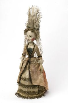 * Doll Great Britain ca. 1680 Wood, gessoed and painted, leather, and satin trimmed with metallic lace and fringe It was carved from wood and covered with gesso (a mixture of plaster and glue) before being painted. The doll is fashionably dressed with a wig made of human hair and beauty spots painted on the face