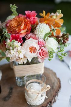 pink, peach and rose wedding florals on top of a piece of wood #centerpieces http://www.weddingchicks.com/2013/10/30/peach-and-cream-garden-wedding/