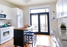 Warm and white kitchen, wooden floors, lots of natural light