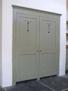 Custom built larder doors with traditional fretwork cut-outs in the top panels. Shown here finished in Farrow & Ball French Gray No.18 These doors were built to conceal an existing built-in alcove