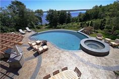 Kideny shaped pool with an infinity edge. Stamped and colored concrete surrounds the pool.