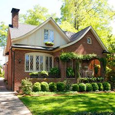 Brick Tudor-style homes are often contrasted with areas of stone, stucco, or wooden claddings on principle gables or upper stories. This home's front gable dormer features half-timbering with stucco infilling. Decorative crossbars add visual interest to the windows.