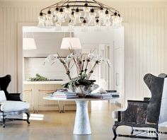The striking dining room features several statement pieces that work beautifully together including wood wing chairs from Lucca Antiques in Los Angeles, a chandelier from Liza Sherman in New York, and a vintage marble table by Angelo Mangiarotti.