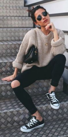 Maria Valdes + black ripped jeans + chunky knitted sweater + rolled at the sleeves + black and white converse + circular framed shades. Sweater: Dylan Kain, Shoes: Converse.