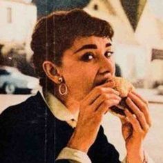 Audrey Hepburn eating a burger