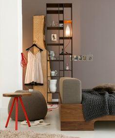 """Dass Grau eine echte Wohlfühlfarbe ist, beweist dieses Schlafzimmer. Den warmen Farbton der graubraunen Wand greifen die Möbel aus massivem Nussbaum auf. Schöne Akzente: das rote Textilkabel und die roten Beine des Hockers.  Die Wandfarbe entspricht beispielsweise der SCHÖNER WOHNEN-Farbe """"04.005.04"""": www.schoener-wohnen-farbe.de  Regal """"Code 1"""", ab ca. 1.035 Euro Bett """"Doze"""", ca. 1.785 Euro Hocker """"SC07"""", 269 Euro alles www.zeitraum-moebel.de"""