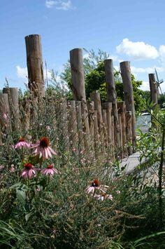 Sfeervolle border met kastanjehouten palen als erfafscheiding. Ontwerp en aanleg hoveniersbedrijf van Elsäcker Tuin