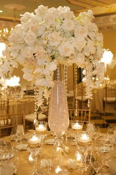 White Wedding Flowers: This grand centerpiece is a definite crowd pleaser, the tall vase is filled with crystals and accented by crystal strands dripping from an arrangement of roses, hydrangeas and orchids.