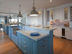 lampe plafond en métal argenté, îlot de cuisine en bois bleu ciel et sol en bois massif assorti