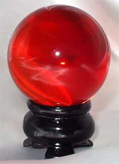 Clear Ruby Red Sphere Crystal Ball - Nice ruby red color to this 50 mm or diameter Crystal Ball. Comes with wooden stand, completely transparent and made from reconstituted quartz crystal. or sphere deep ruby red color!