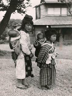 """ねんねんころりよ 子守をする少女たち   ナショナルジオグラフィック日本版サイト ナショナル ジオグラフィック協会 写真資料室から ねんねんころりよ 子守をする少女たち 赤ん坊をおぶった少女が2人。小さな弟か妹の子守をしているところだろうか。「日本では""""おんぶ""""が乳母車の代わり」という説明とともに、1933(昭和8)年3月号に掲載された。"""