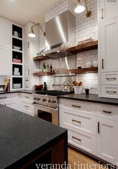 White cabinets, leathered black granite, reclaimed wood shelving