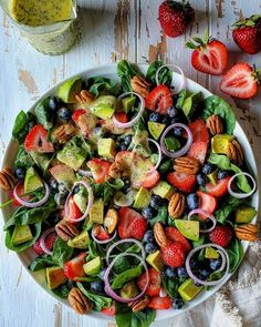 Spinach Strawberry Salad is a summer stunner! Strawberries, blueberries, and avocado all pair beautifully with a homemade lemon poppyseed dressing.