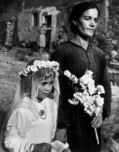 W. Eugene Smith. Spain. Extremadura. Province of Caceres. Deleitosa. 1951. Lorenza Curiel (7 years old), dressed for her First Communion, going to church with her mother.