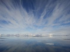 Photo: Wispy clouds over an island in the Svalbard Archipelago