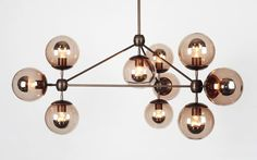 Modo chandelier is made of machined aluminium and glass. The chandelier has three sides and incorporates ten globe lights. The Modo chandelier is inspired by of
