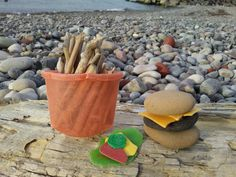 "My ""vegan"" burger & french fries rock sculpture, made from beach rocks and assorted plastic debris found at the Lake Erie shoreline. Notice the red ketchup, yellow mustard, green pickle, yellow-green lettuce, and golden ""vegan"" cheeze -- all pieces of plastic junk found in the sand. Same for the crushed orange cup, which was perfect for the french fry holder. Beach plastic is a very sad reality, unfortunately."