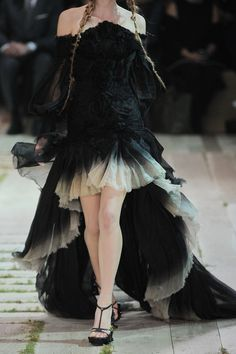Alexander McQueen SS 2011Off-the-shoulder gown: black silk-organza, peaked at front of bodice with internal underwired and boned mesh, raw finish, long and loose sheer sleeves, heavily ruched, button-fastening cuffs, dégradé cream hem, ruched strips at skirt, train, fully lined.