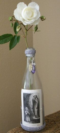 This feminine bud vase is made from a vintage bottle (patina included), upon which is featured an antique French holy card dated 1872. The card rests atop pretty sheer lavender ribbon and the bottle is trimmed in beautiful shades of lavender and silver. Hanging from the neck of the bottle is a vintage medal from Lourdes, France, accompanied by a large lavender pendant bead and a small crystal bead.