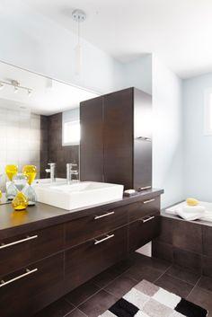 L'utilisation d'un seul matériau, et d'un seul choix de couleur, le concept de cette salle de bains attire notre regard… sans toutefois voler la vedette aux autres éléments de cette pièce! Les armoires de la salle de bains de style panneaux plats ont été réalisées en mélamine horizontale. Le tout est harmonisé avec un comptoir en stratifié.
