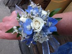 Wrist corsage of blue delphinium, white spray roses and white caspia.
