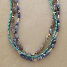 Multi-strand necklace. Each strand a completely different type/size of stone. Similar color tones. Some silver accents.