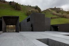 A charcoal-hued pool complex rises from the ashes of a former sports field in Povoação, Portugal—a town know for its volcanic beach. Slabs of monolithic-sized basalt rock emerge from the nearby hillside and run alongside the slope as if a continuation of it.