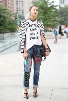 an edgy street style look, street fashion, boyfriend style jeans with patches, white tee with a black caption and a black and white striped cardigan,