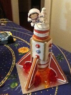 A gingerbread 3D rocket! I made this using a template for the 4 base parts, then stacks of gingerbread circles with a hollow gingerbread rectangle between. Red and orange cellophane created flames, and the space man is a candle!