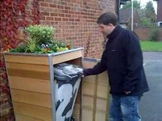 starting to rock the bin back on its wheels Inventor Nick Staley shows how easy it is to remove the garbage can from the full size secret shed prototype that camoflages the wheelie bin well
