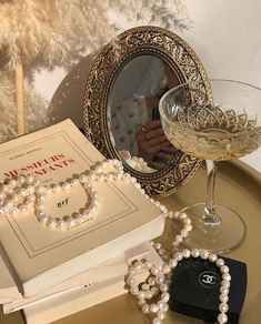 A golden table with pearls, chanel makeup, an aesthetic / vintage mirror, books. Golden, shiny wine in clear fancy wine glass next to books Cream Aesthetic, Boujee Aesthetic, Brown Aesthetic, Aesthetic Vintage, Aesthetic Photo, Aesthetic Pictures, Aesthetic Makeup, Summer Aesthetic, Photo Wall Collage
